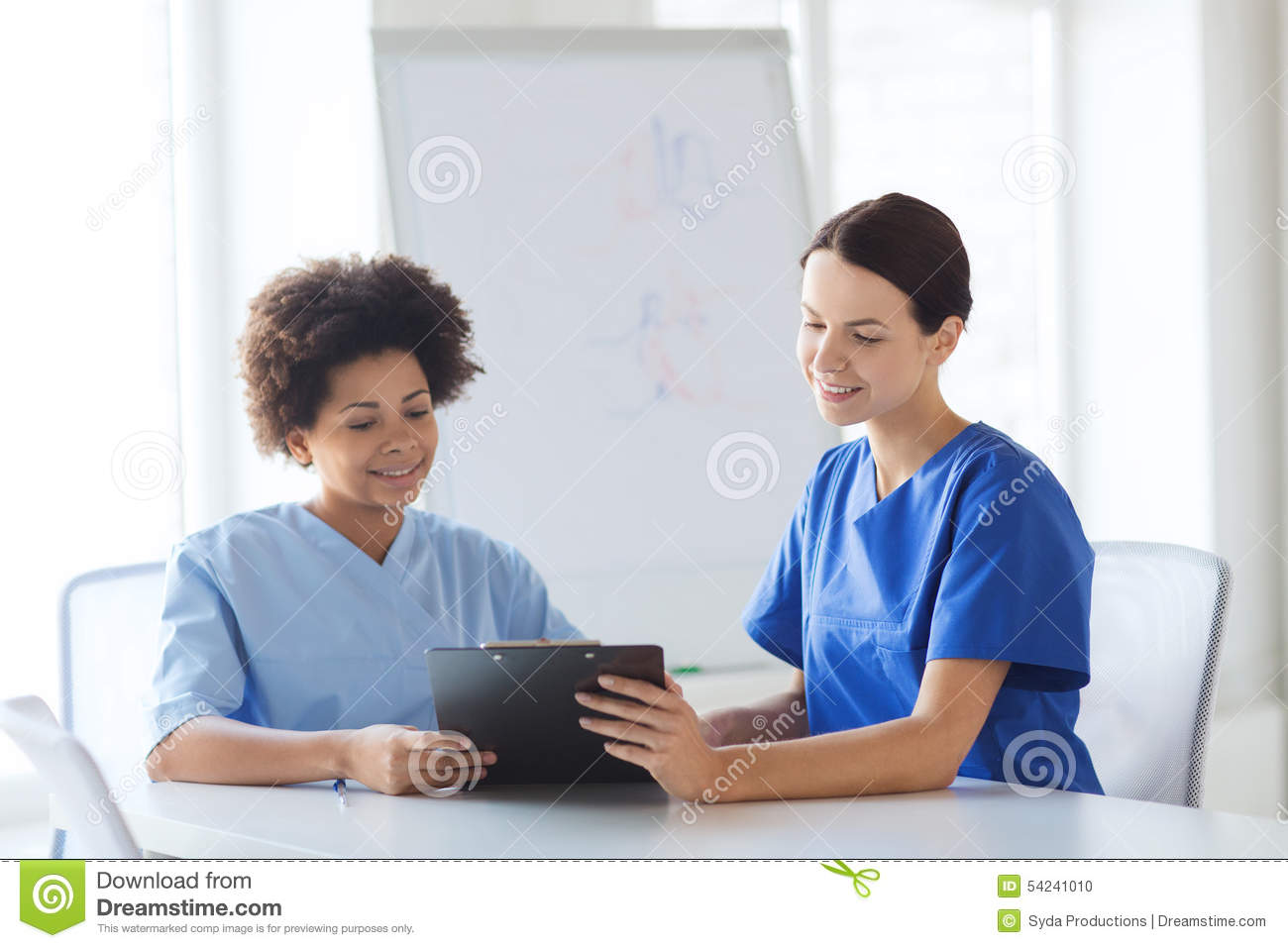 Happy doctors with tablet pc meeting at hospital