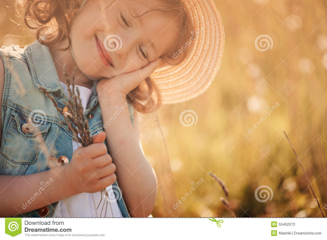 Happy dreaming child girl holding bouquet in summer