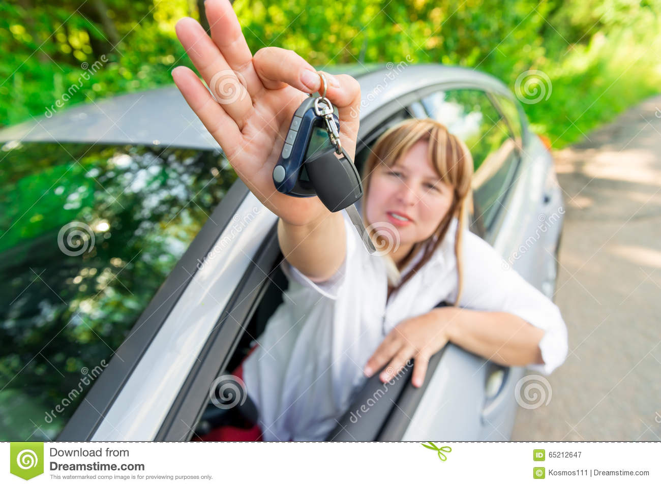 Happy driver showing the key of the car
