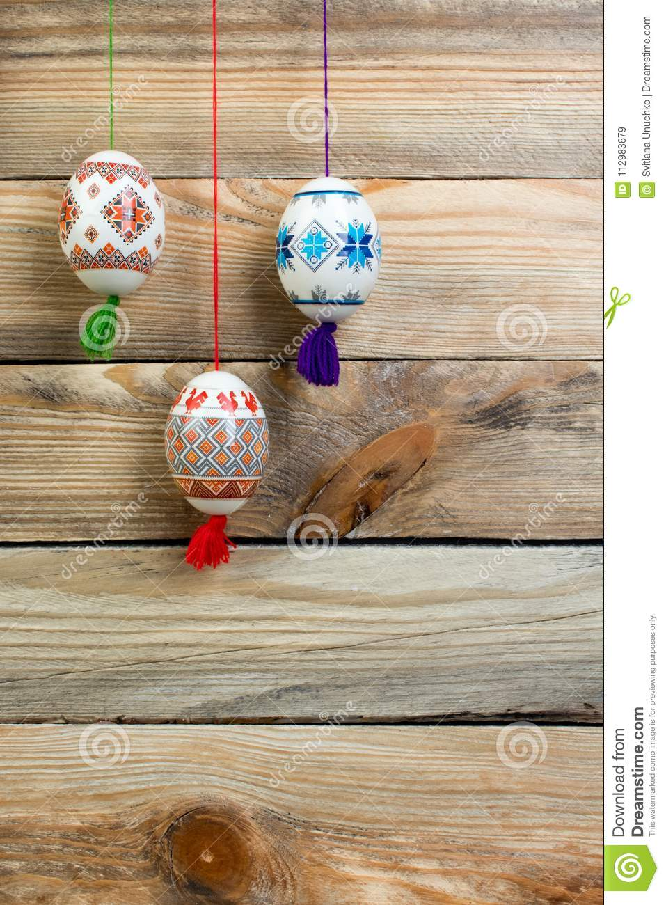 Happy Easter card. Colorful shiny easter eggs on wooden table background. Copy space for text.