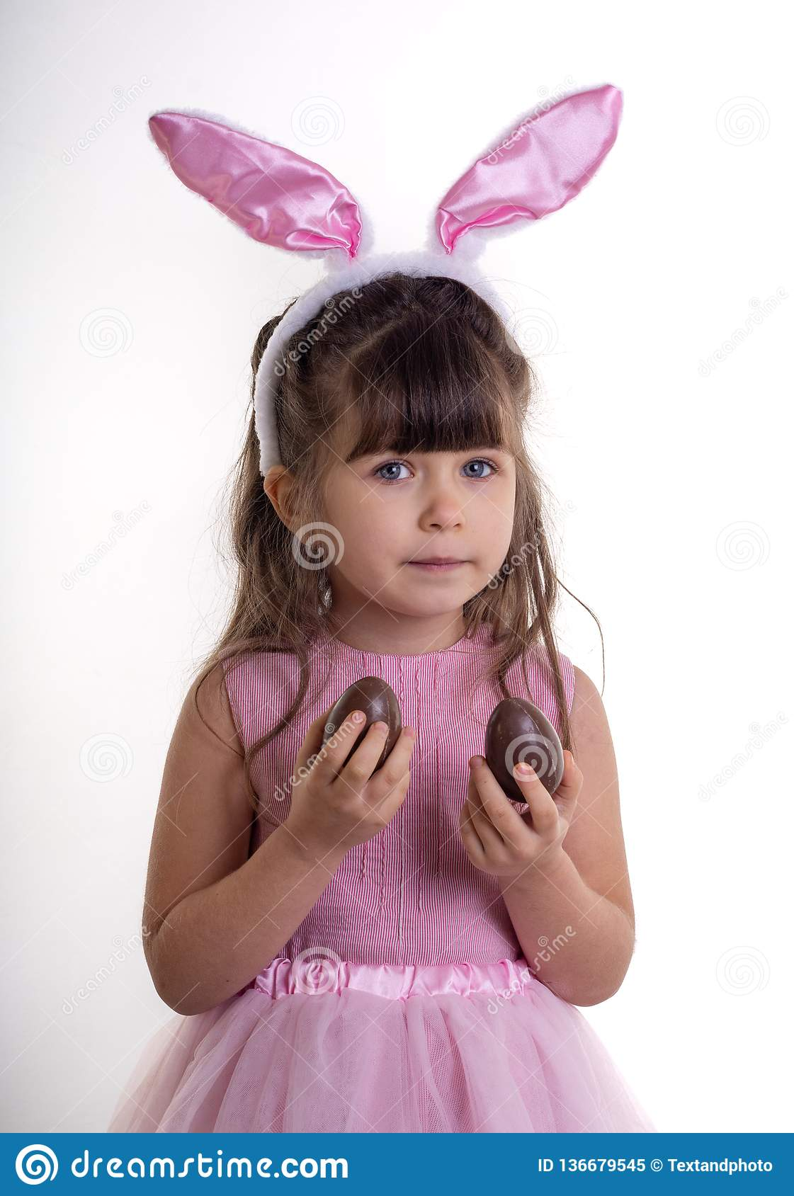 Happy easter! Child girl with bunny ears and chocolate eggs. Isolated on white.