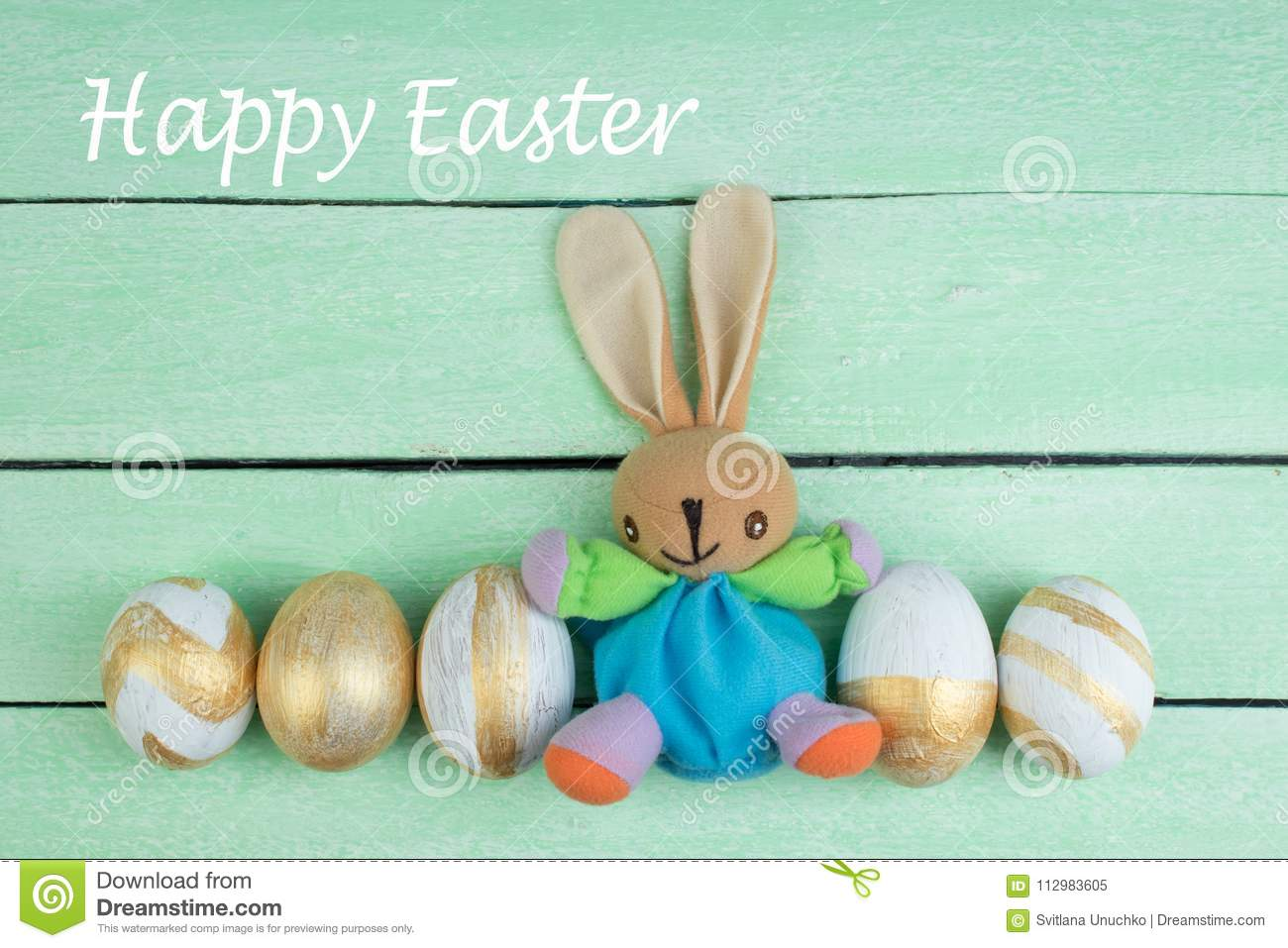 Happy Easter. Colorful easter eggs and rabbit on wooden background.