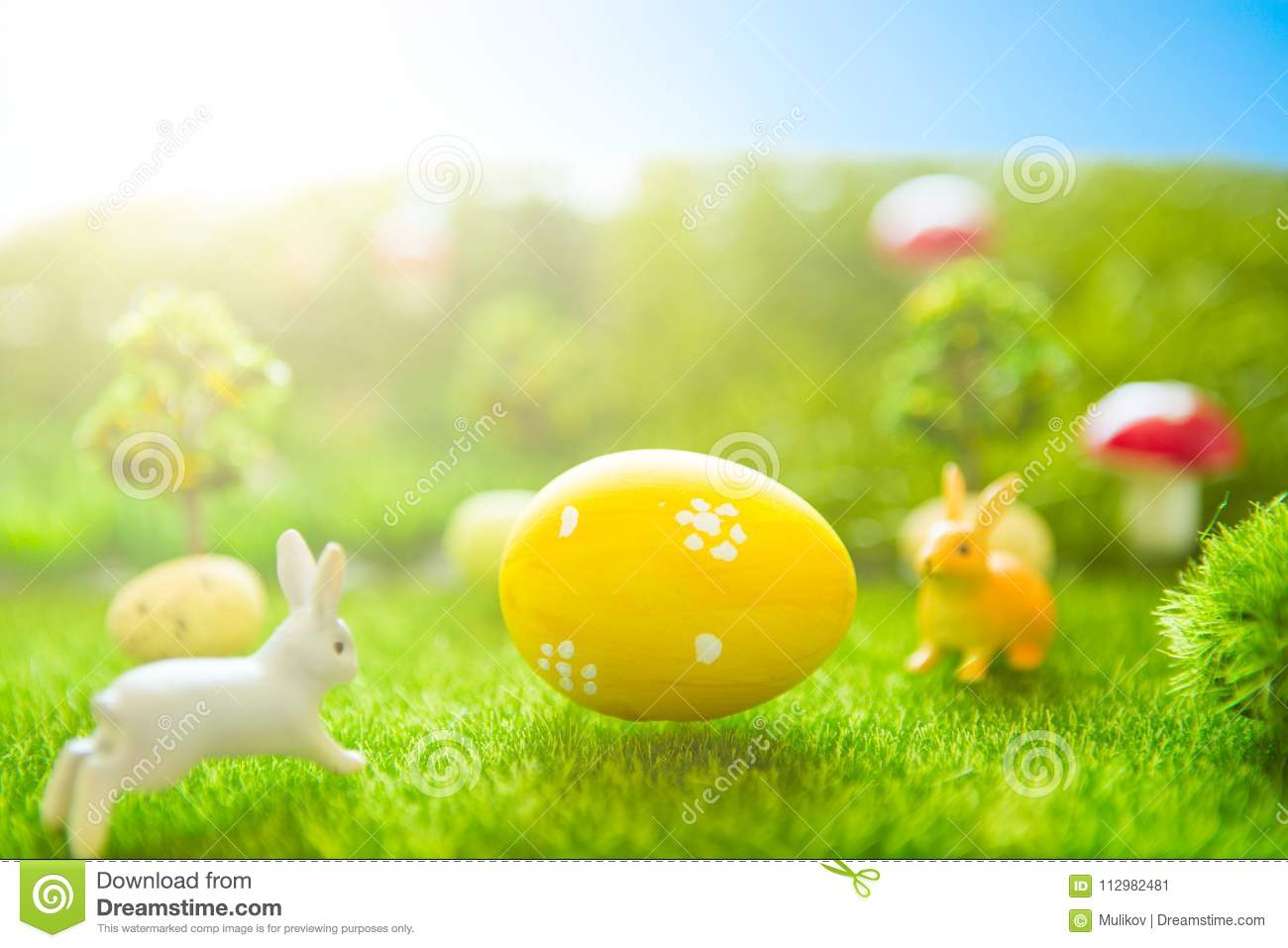 Happy Easter concept. Easter bunny and Easter eggs on green grass. Fairy tale sunset on the plastic green field with plastic grass