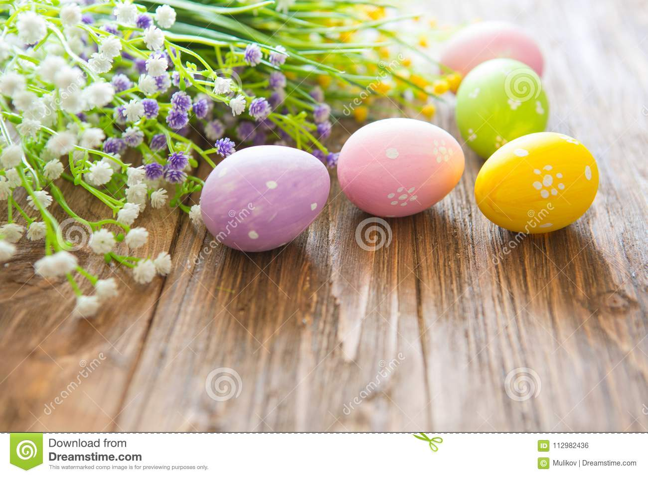 Happy Easter concept. Colorful easter eggs and flowers on wooden plank