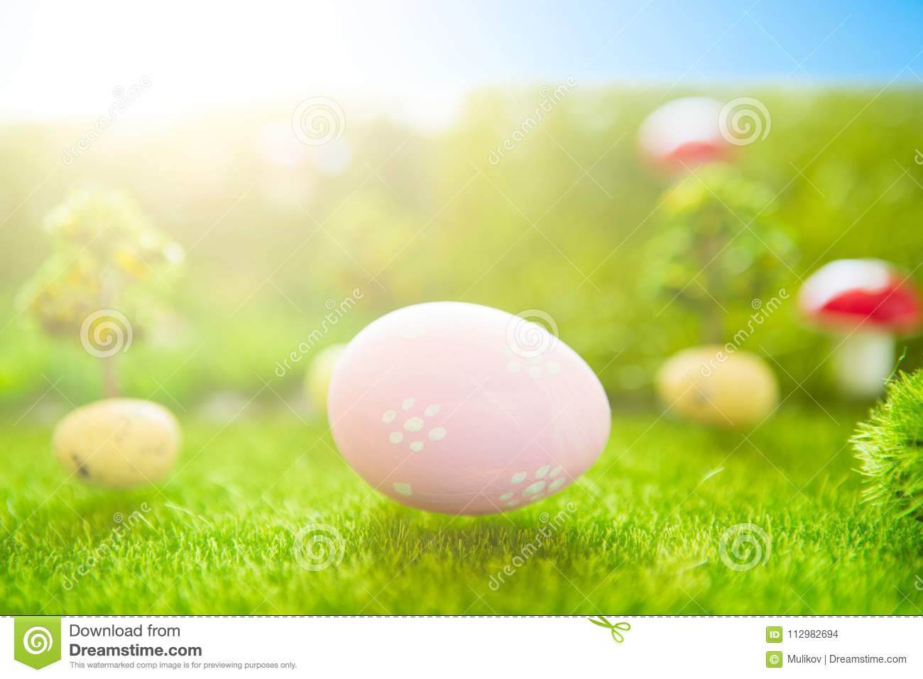 Happy Easter concept. Colorful easter eggs and one big pink easter egg on spring green grass. Fairy tale sunset on the plastic gre