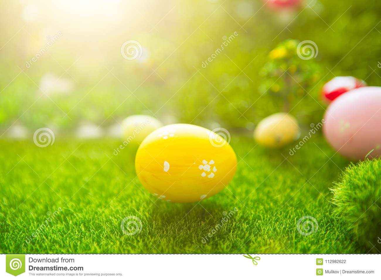 Happy Easter concept. Colorful easter eggs and one big yellow easter egg on spring green grass. Fairy tale sunset on the plastic g