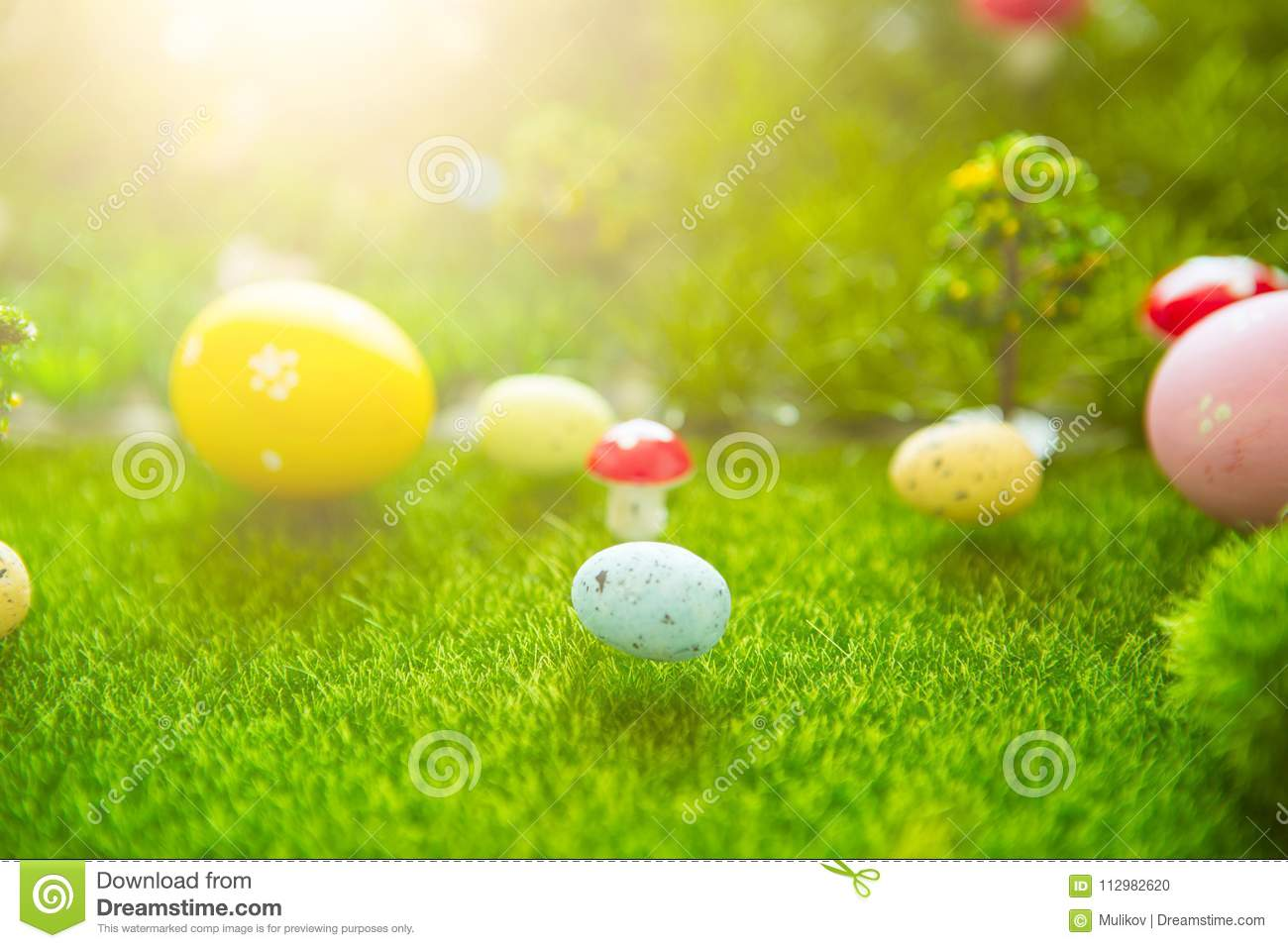 Happy Easter concept. Easter eggs on green grass. Fairy tale sunset on the plastic green field with plastic grass, mushrooms and t
