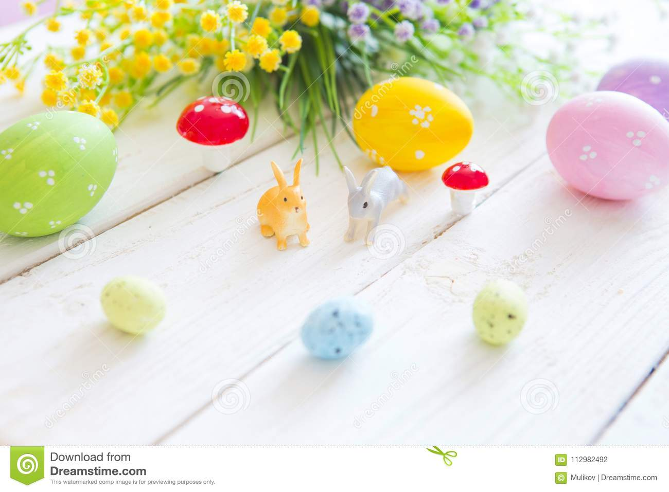 Happy Easter concept. Easter greeting card with flowers, easter rabbits bunny toys and eggs on white wooden plank
