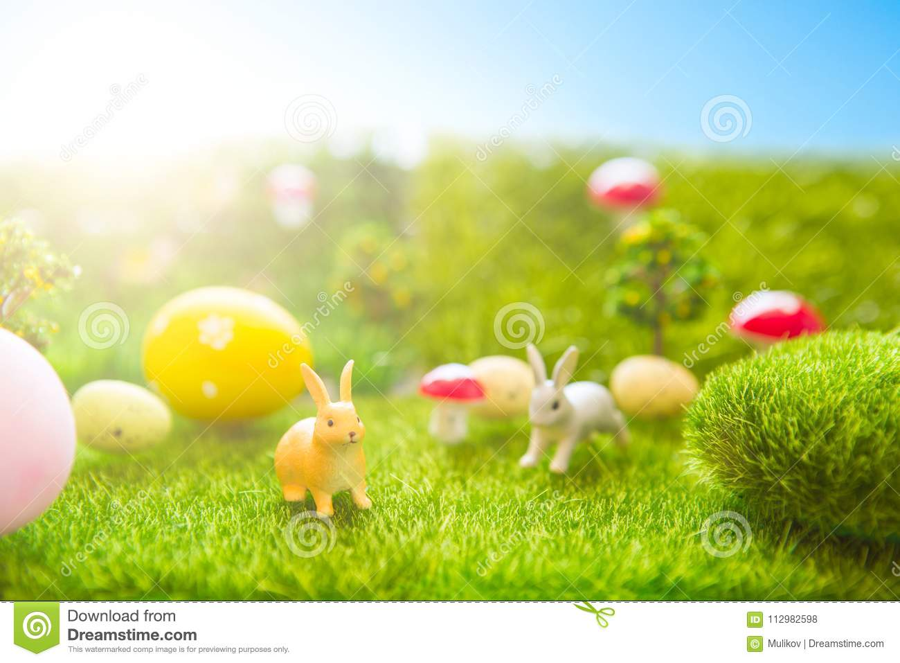 Happy Easter concept. Easter rabbits toy on spring green grass. Fairy tale sunset on the plastic green field with plastic grass, m