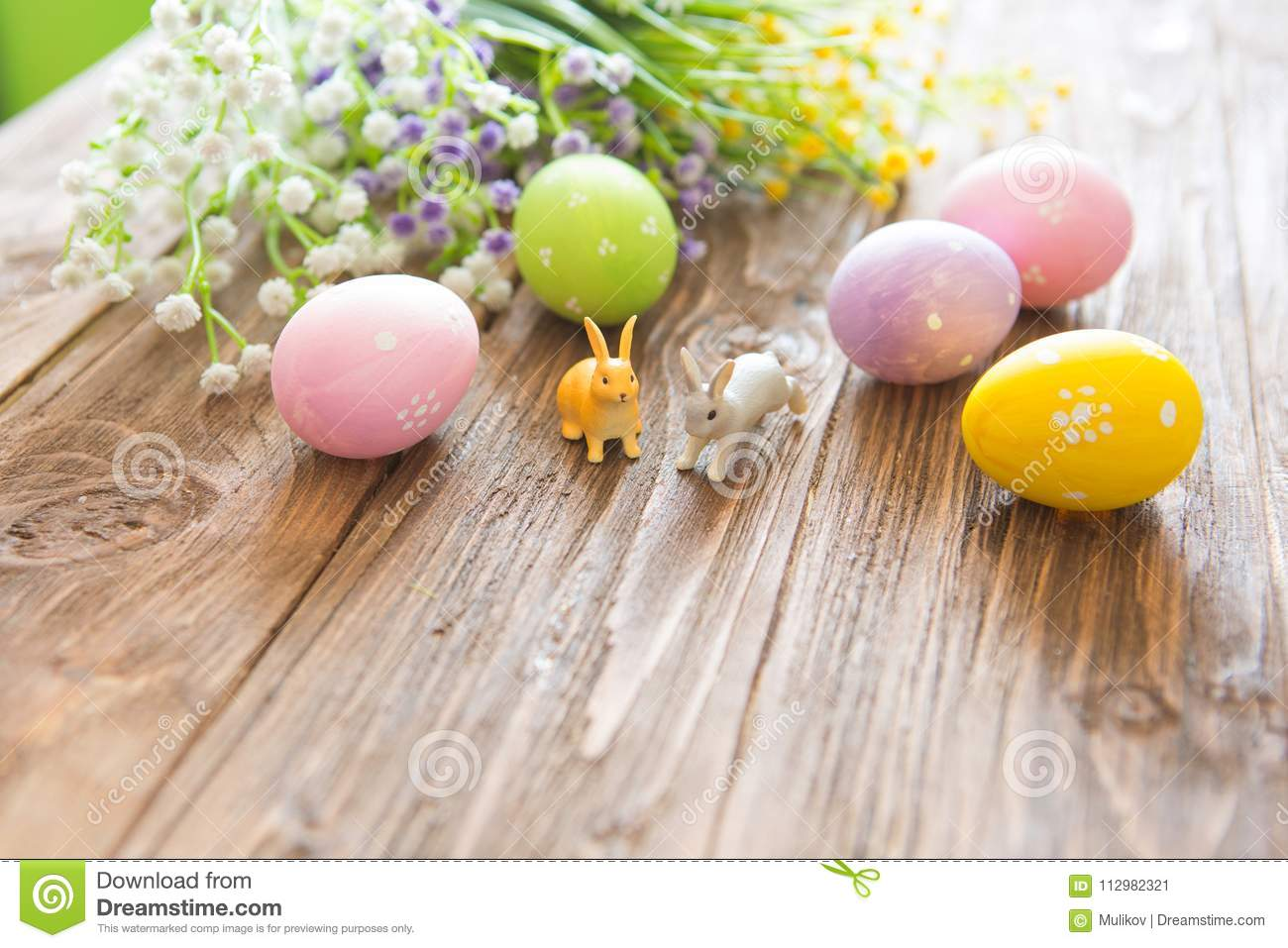 Happy Easter concept. Easter eggs with flowers and small bunny toys on wooden board, easter holiday concept