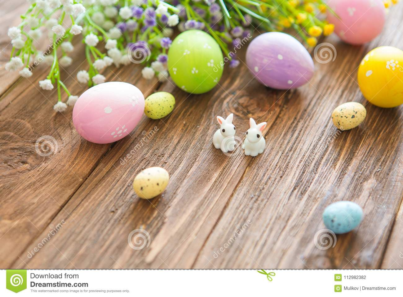 Happy Easter concept. Rabbits with easter eggs on wooden table. Cute Little easter bunny