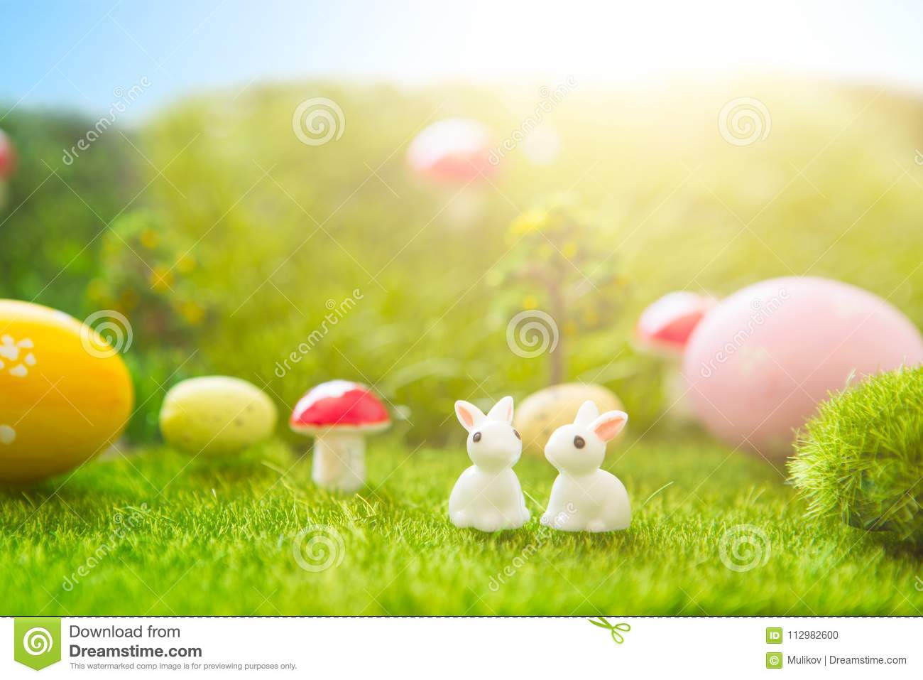Happy Easter concept. Easter rabbits toys with easter eggs on green grass. Fairy tale sunset on the plastic green field with plast