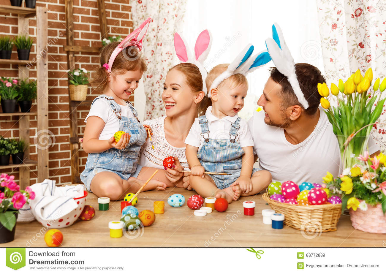 Happy easter! family mother, father and children paint eggs for