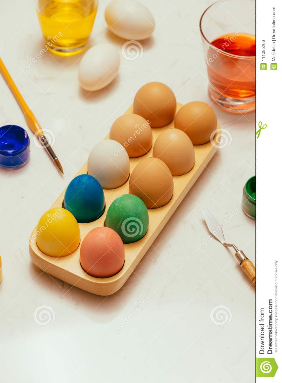 Happy Easter! Friends painting Easter eggs on table.