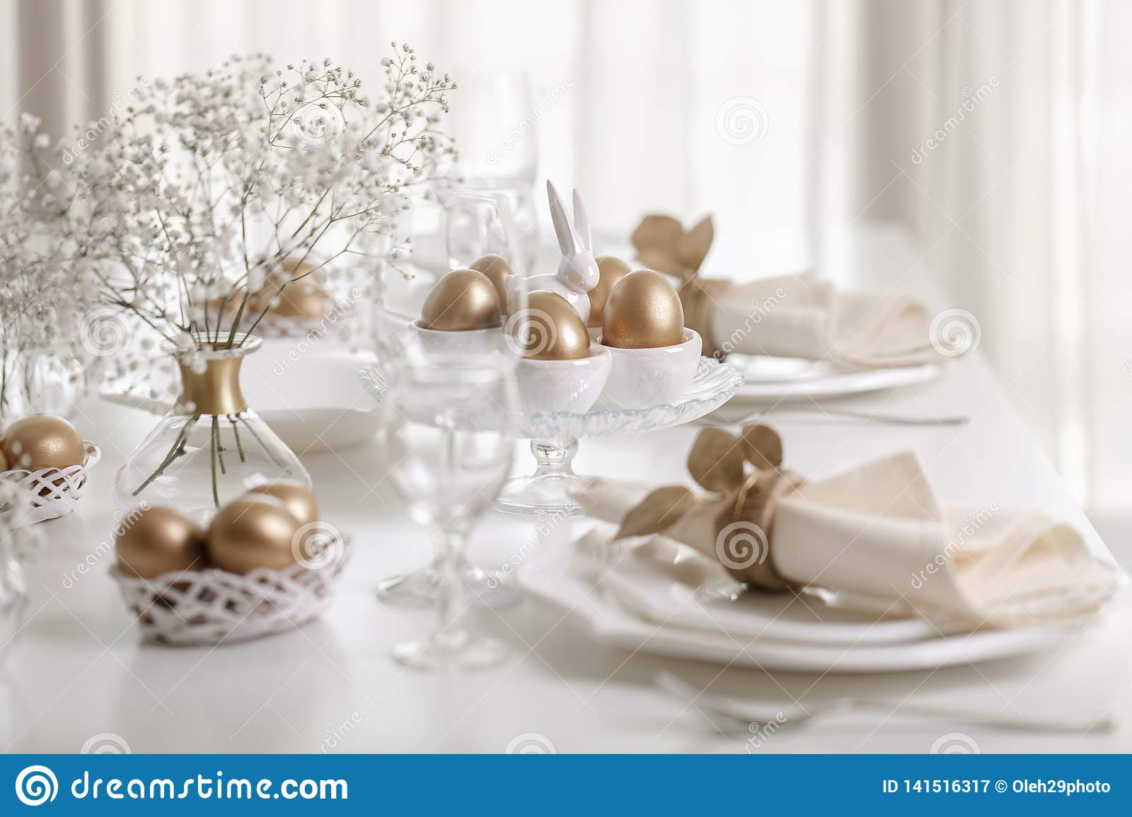 Happy Easter! Golden decor and table setting of the Easter table with white dishes of white color