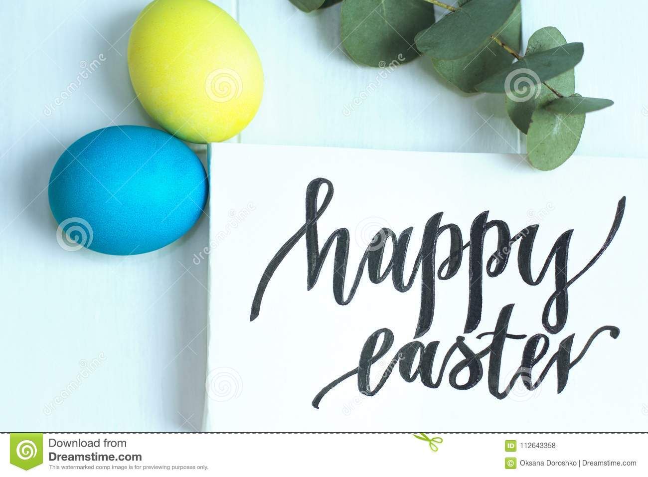 Happy Easter inscription, yellow and blue eggs on a white wooden background