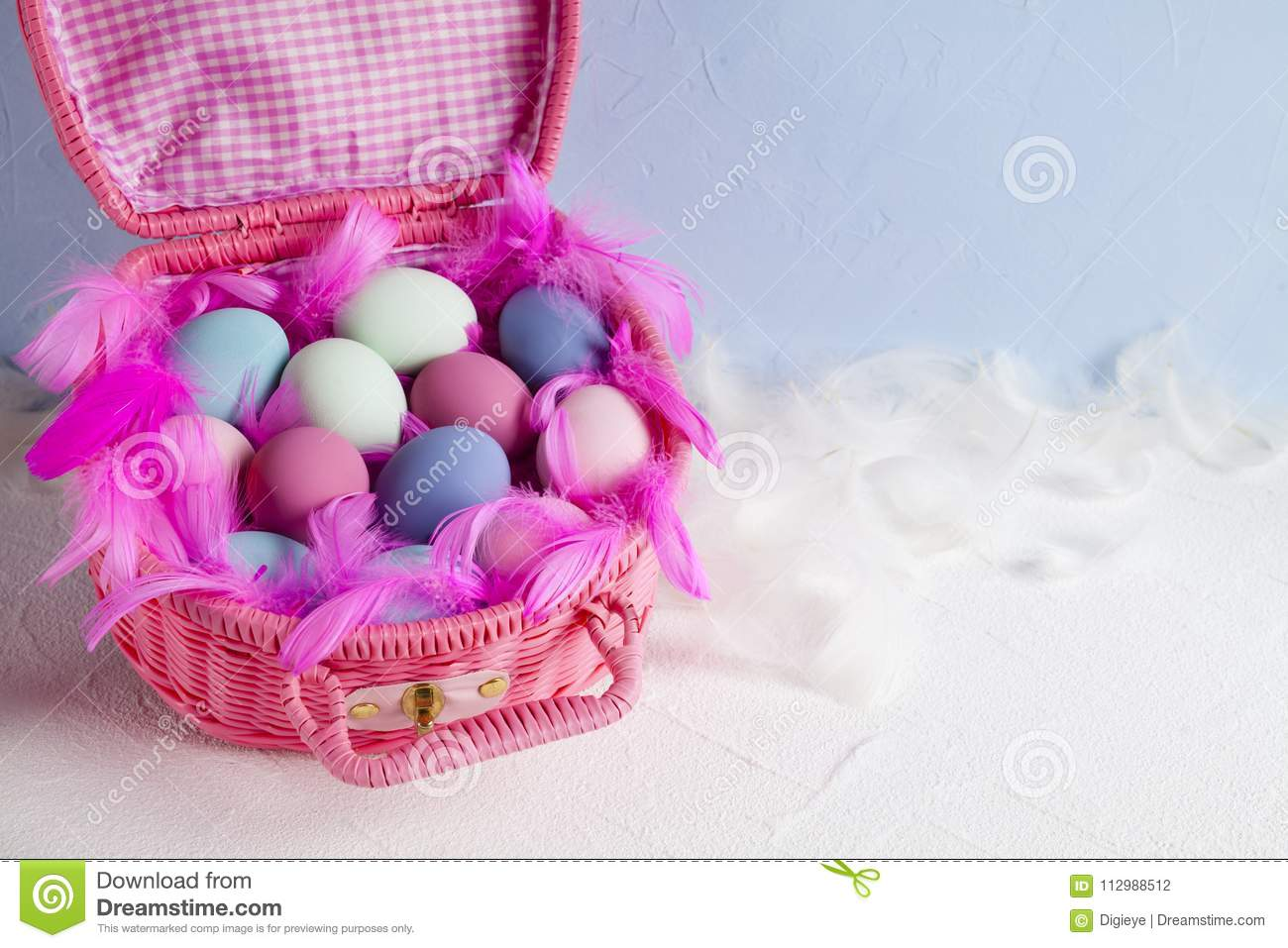Happy Easter - pink basket full of colored eggs and feathers