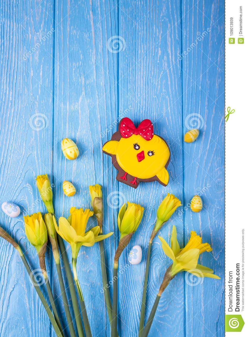 Happy Easter. Spring flowers yellow daffodils, easter eggs and gingerbread chicken on a blue background. Top view, free space