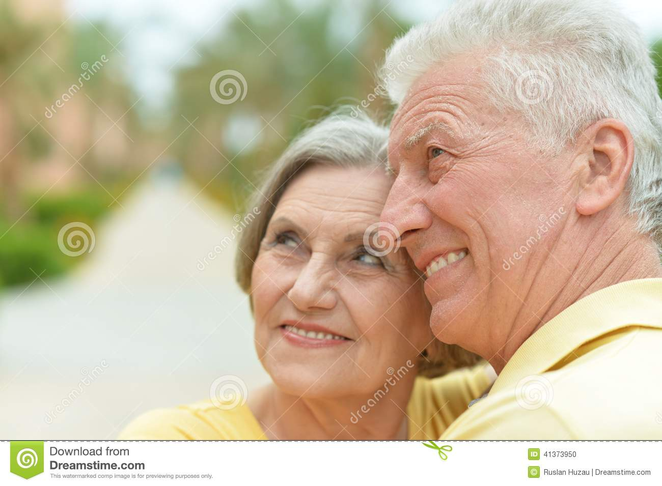 Happy elderly couple at nature on leaves background Happy Elderly Couple