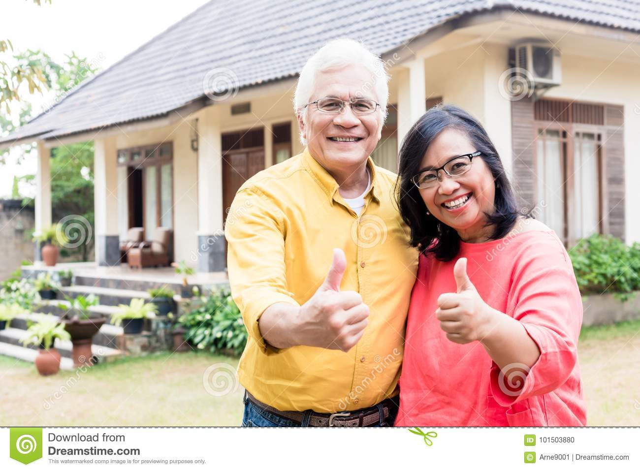 Happy elderly couple showing thumbs up in front of their new res