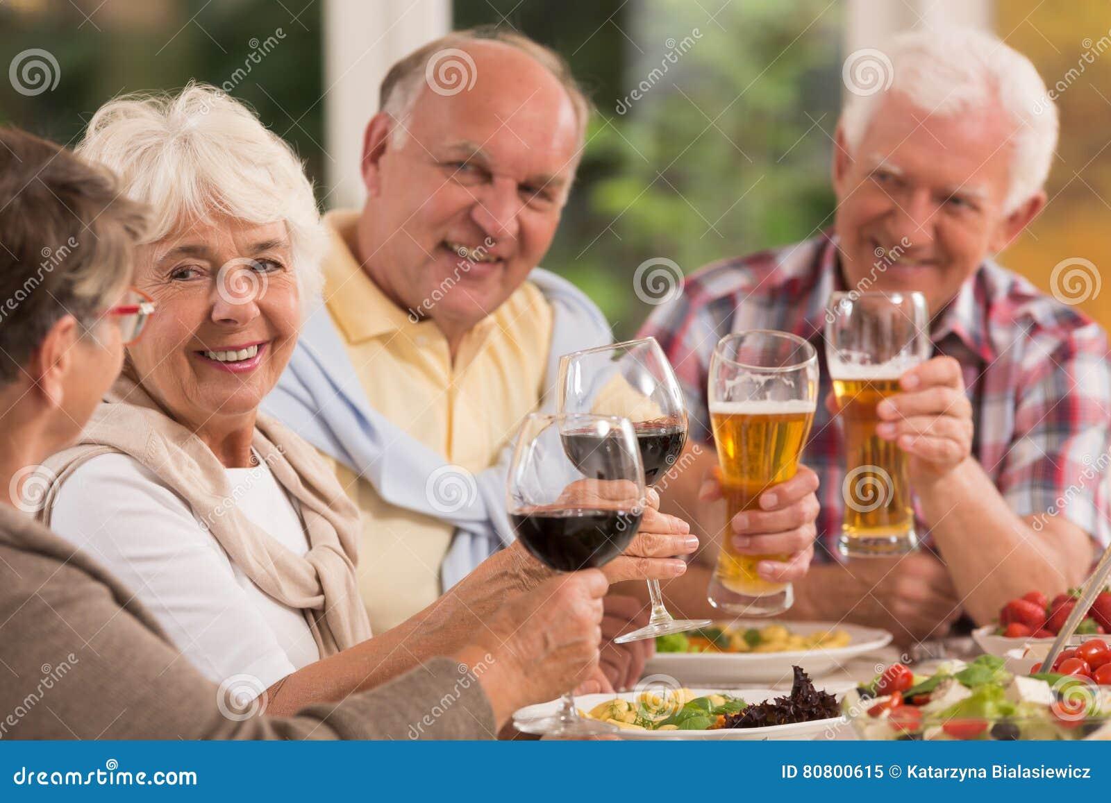 Happy elderly friends drinking beer