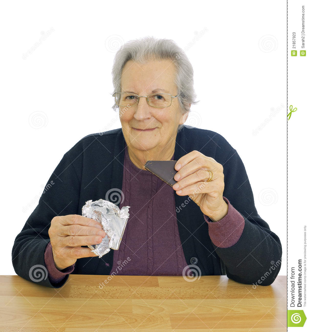 Happy Elderly Lady Enjoys Eating Chocolate Stock Photos