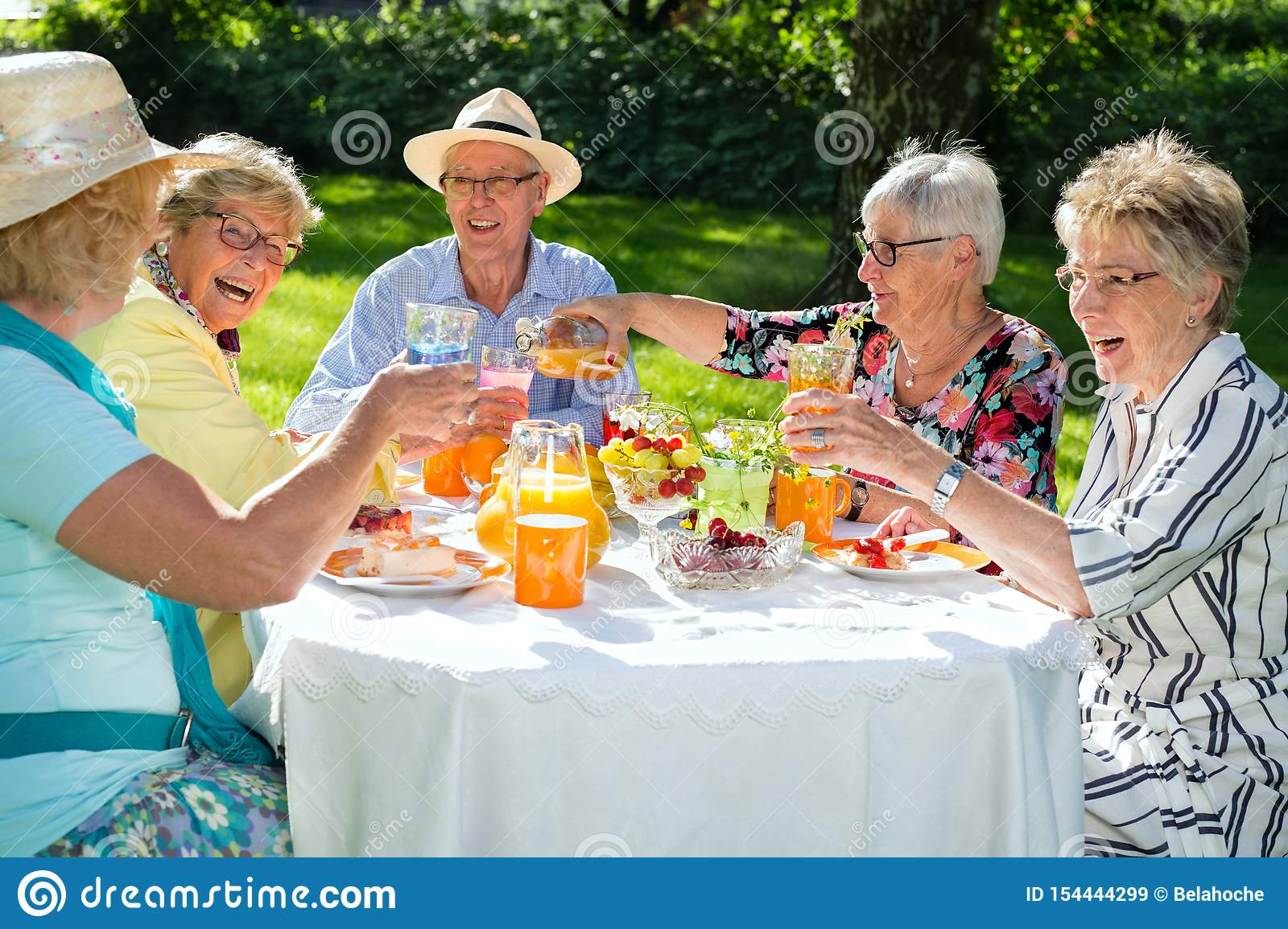 Group Of Mature Friends Enjoying Meal At Rooftop ... |Old People Sitting Around Drinking