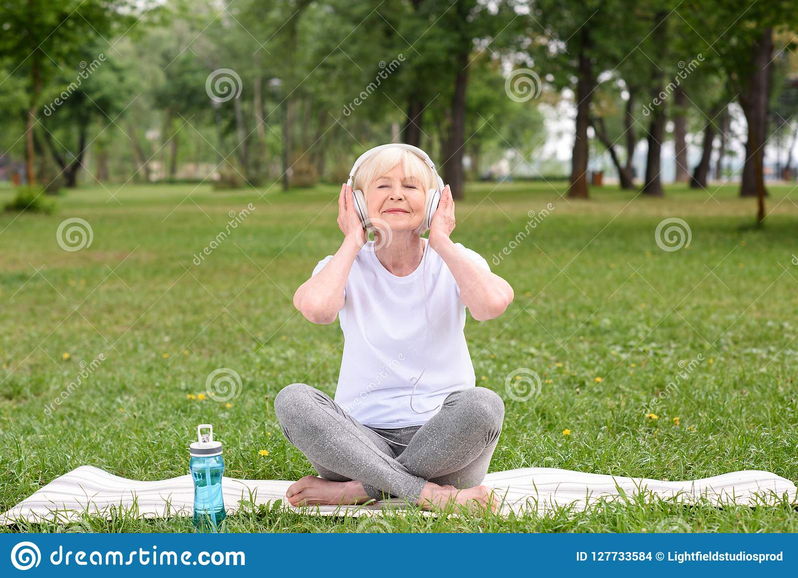 happy elderly woman listening music with headphones while sitting on yoga mat with bottle of water