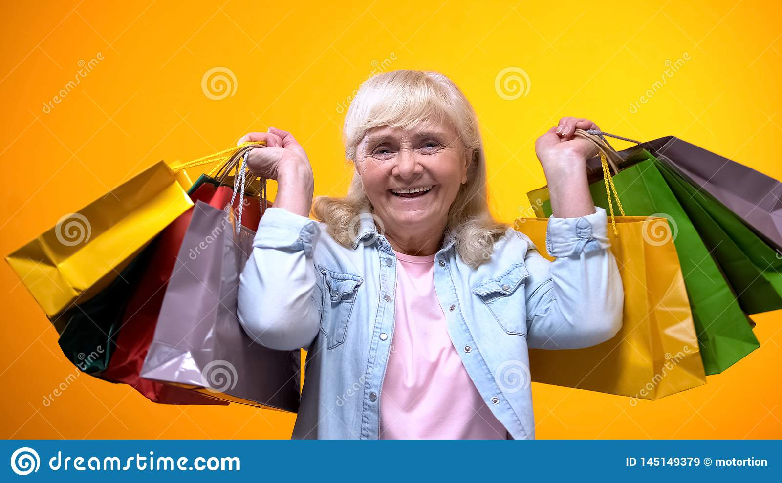 Happy elderly woman showing many shopping bags, leisure time, spending money
