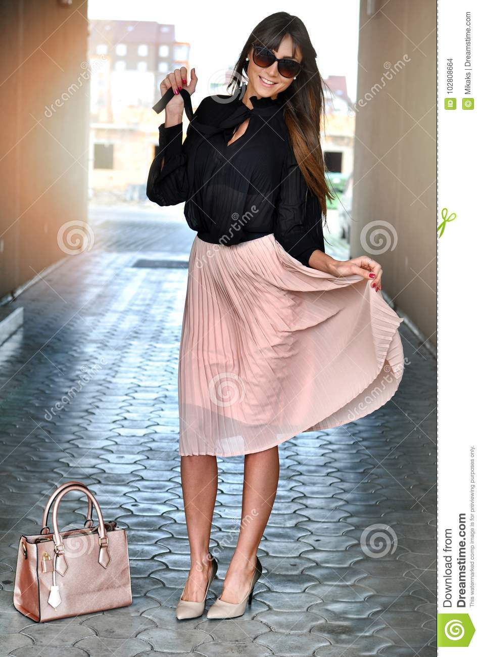8a012990e Happy elegant brunette woman with sunglasses wearing a pink pleated skirt ,black  blouse, high pink-black heels, leather bag. Elegant outfit for every ...