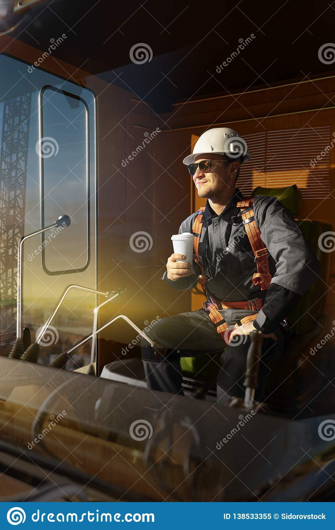 Happy engineer feel success after good work. He sit a top in crane cabin drink hot coffee and looking beautiful sunset