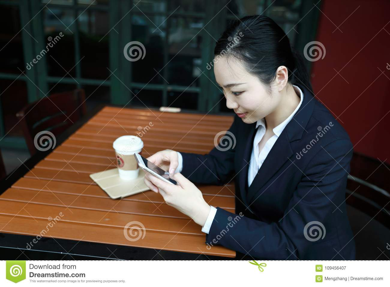 Young woman sitting in coffee shop at wooden table, drinking coffee and using smartphone.On table is laptop