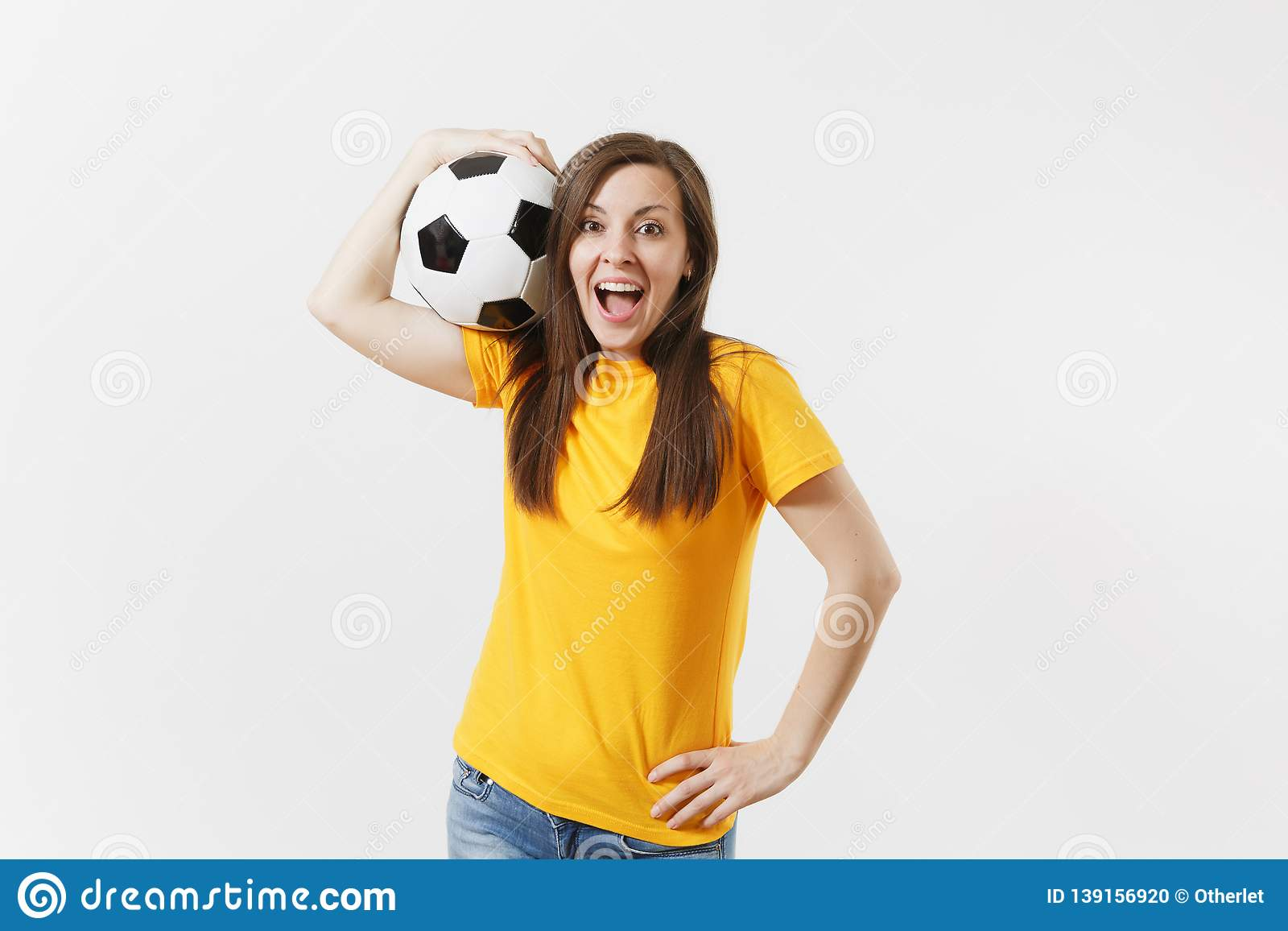 Happy European young woman, football fan or player in yellow uniform holding soccer ball support favorite team isolated
