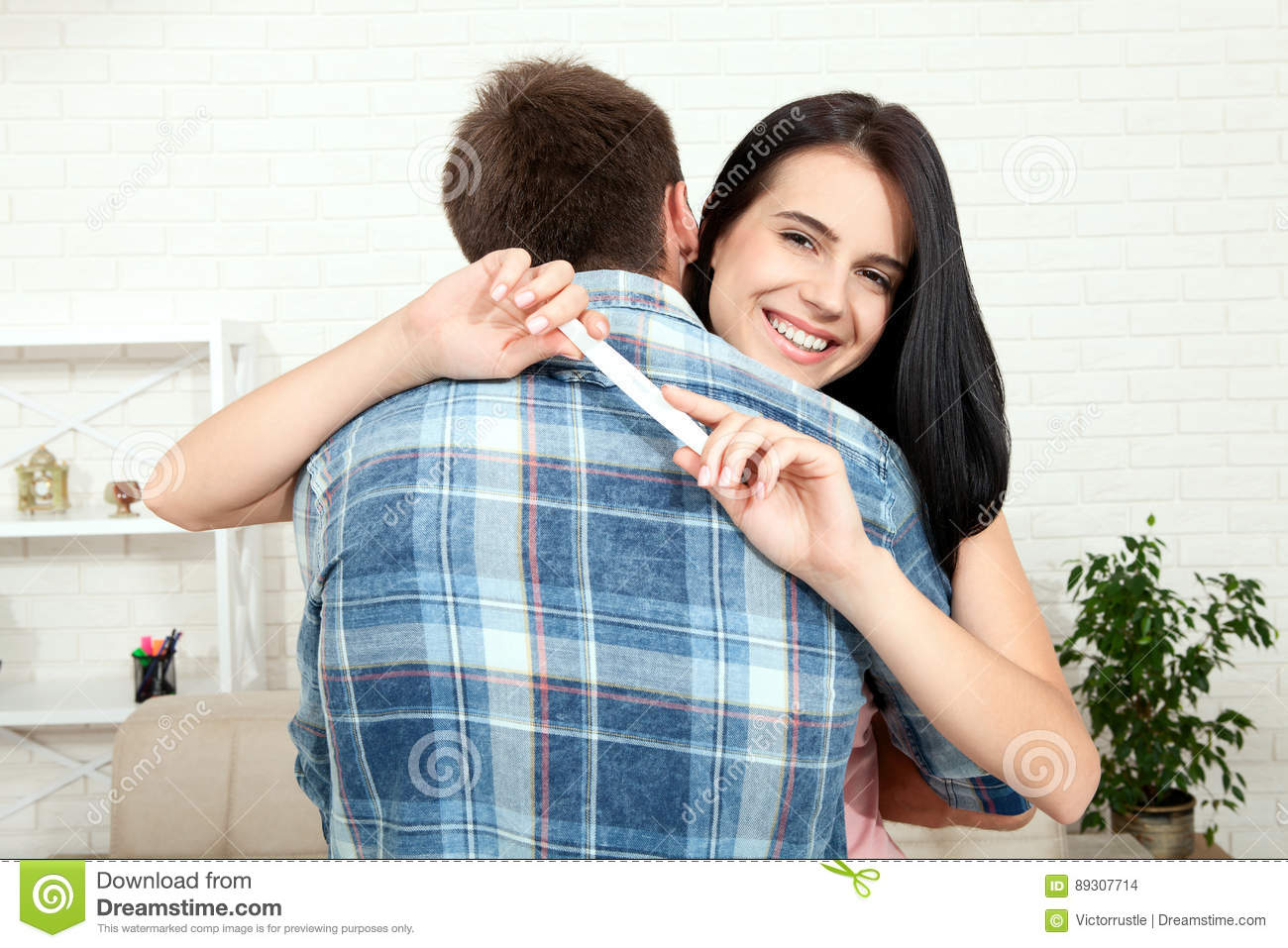 Happy excited couple making positive pregnancy test and celebrating
