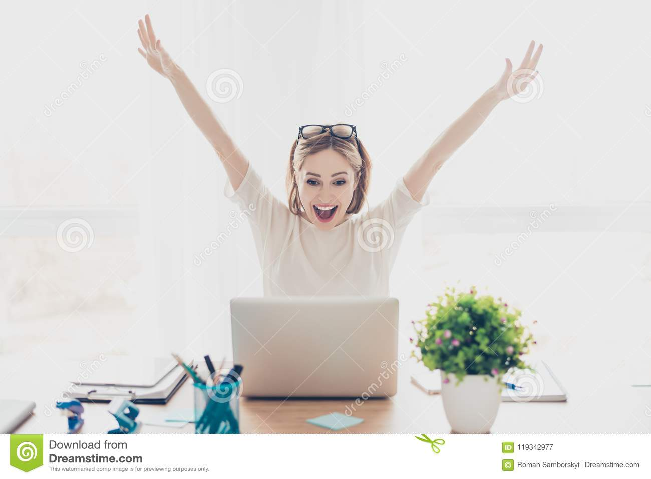 Happy excited successful businesswoman triumphing with laptop sitting at workstation workplace sitting at table in light room rais