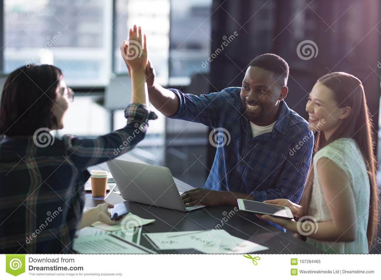 Happy executives giving high five to each other