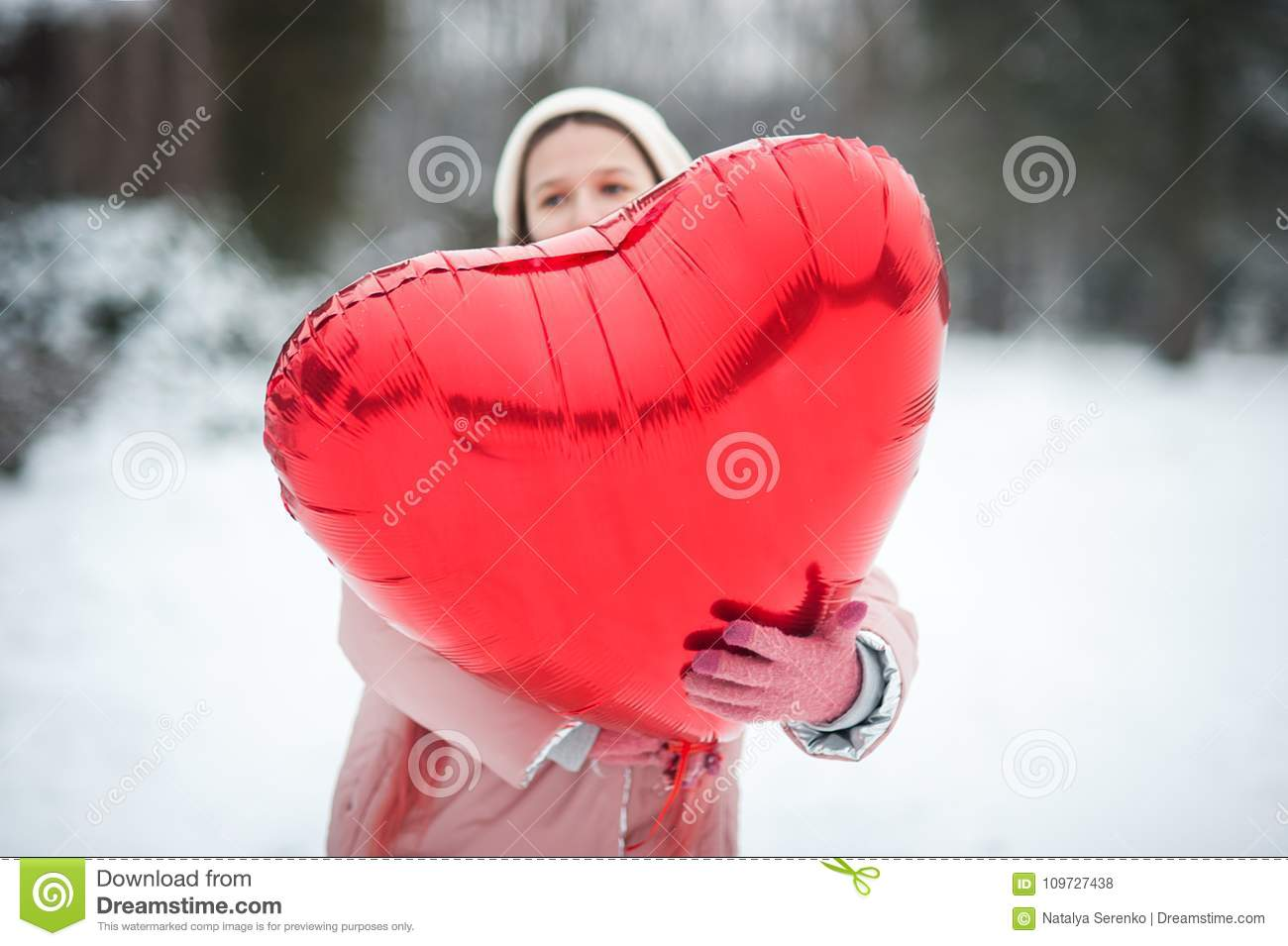 Happy exited girl with Valentine heart balloons outdoor. Valentine`s day concept. Copy space.