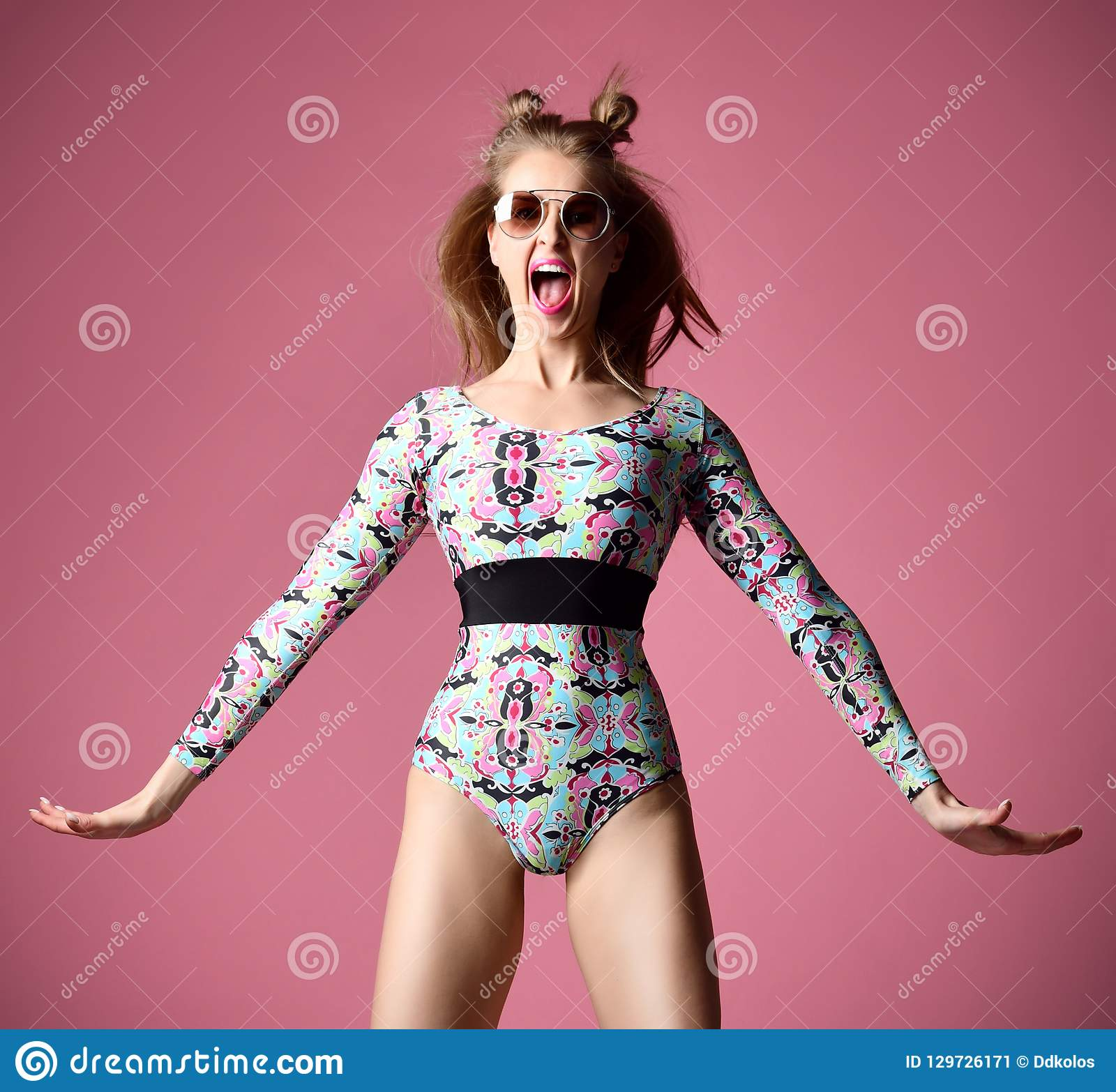 Happy exited pretty yelling woman in sunglasses funny jumping near pink wall.