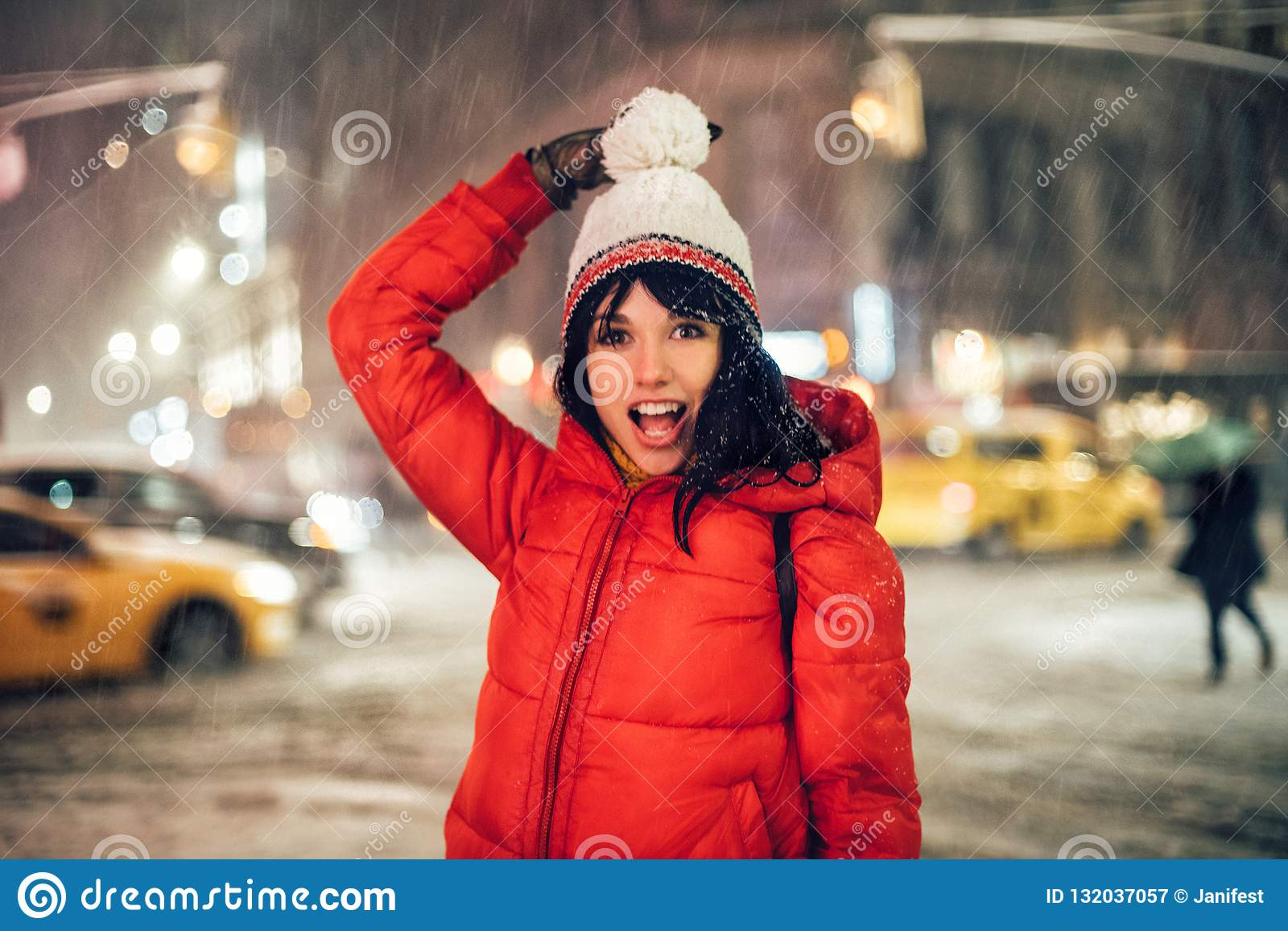 Happy exited woman having fun on city street of New York under the snow at winter time wearing hat and jacket.