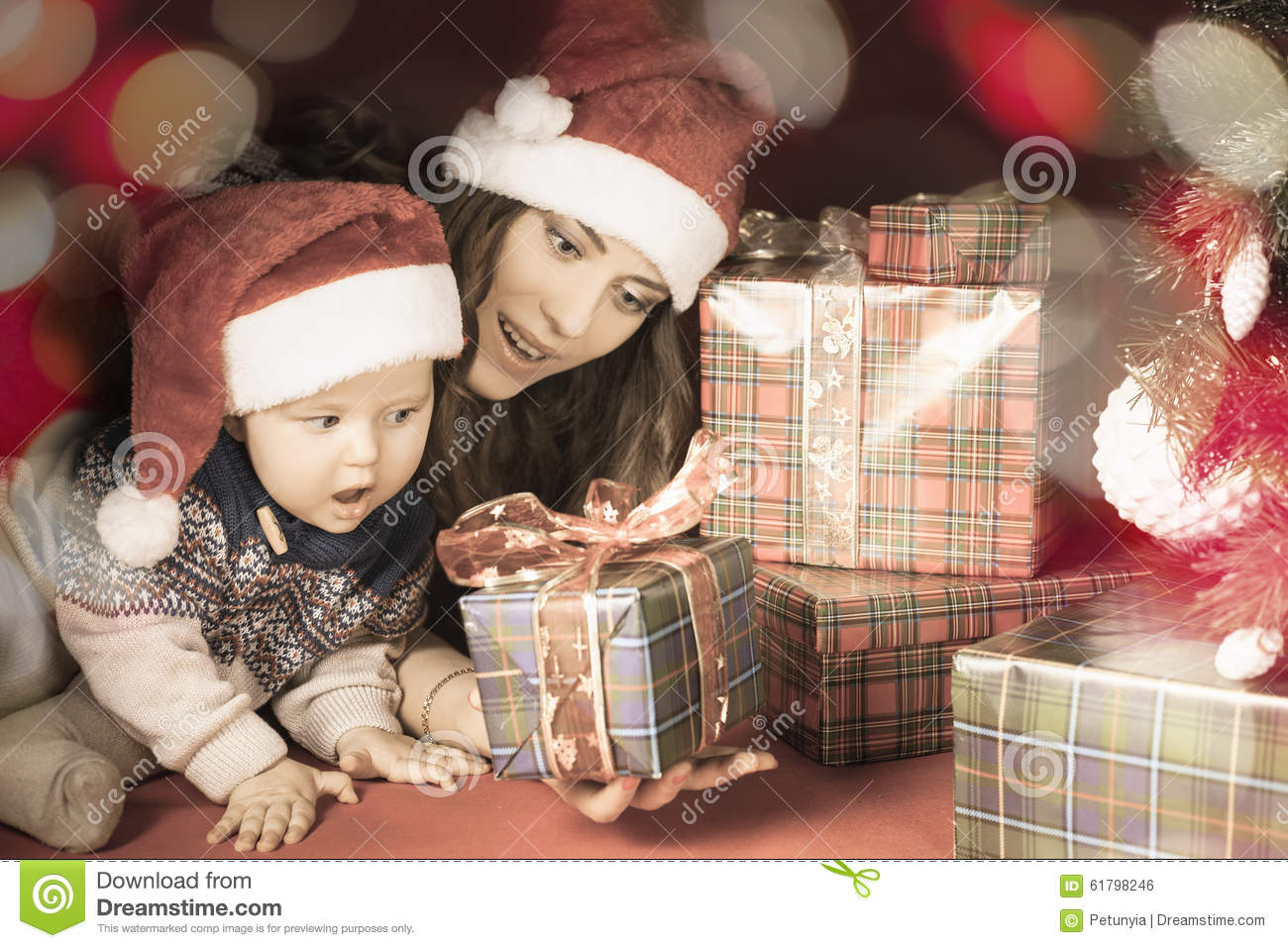 Mother And Baby Gift Box : Happy family of baby and mother near the christmas tree