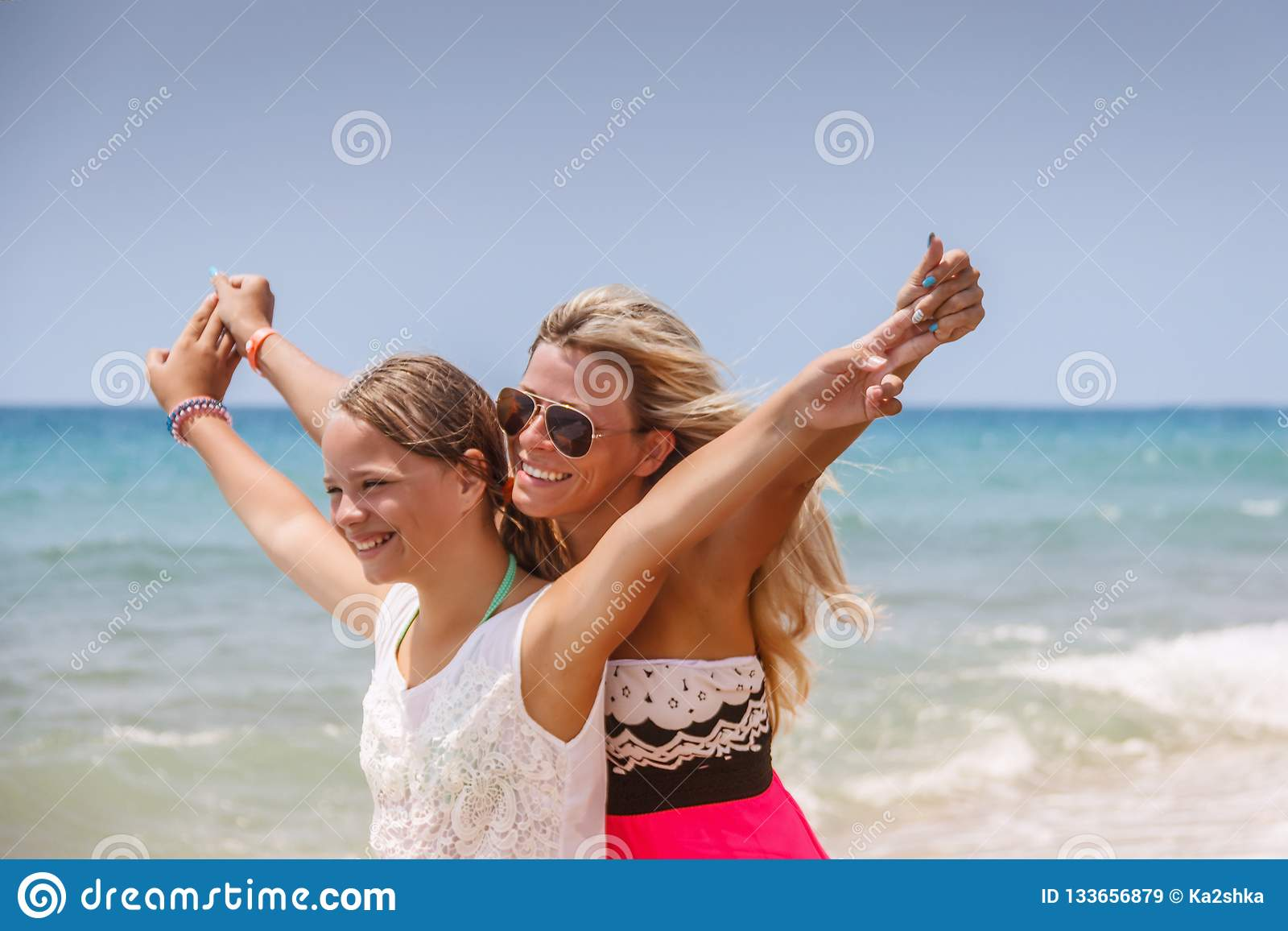 Happy family on the beach. People having fun on summer vacation. Mother and child against blue sea and sky background. Holiday