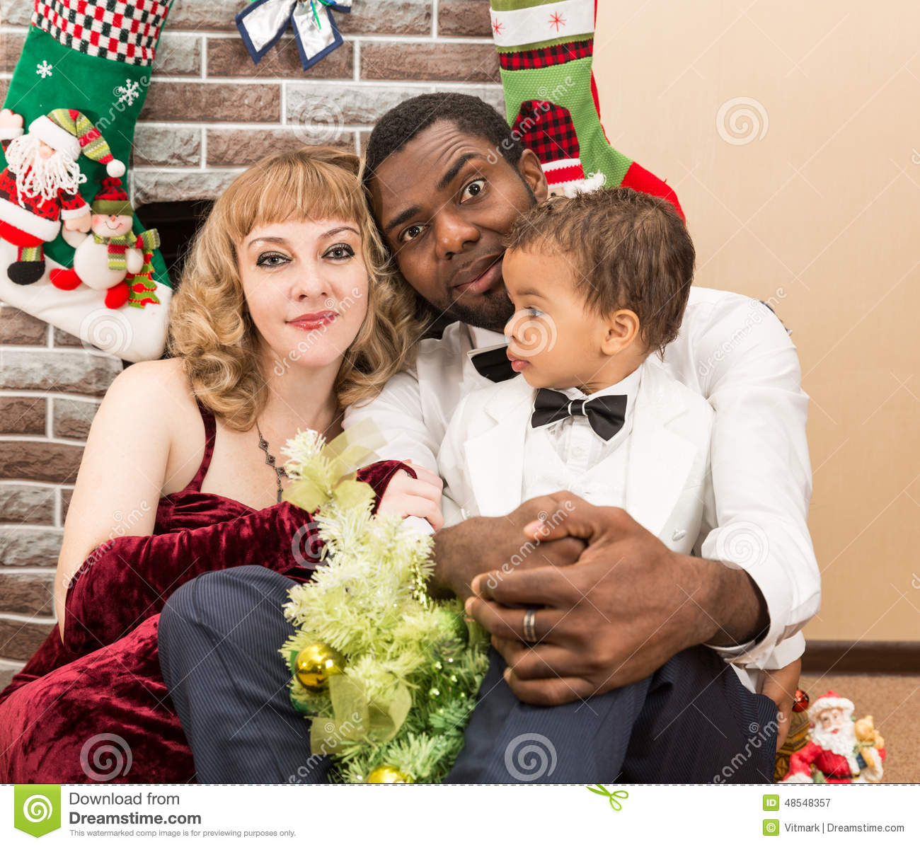 happy family black father mom and baby boy by fireplace christmas - Black Family Christmas Pictures