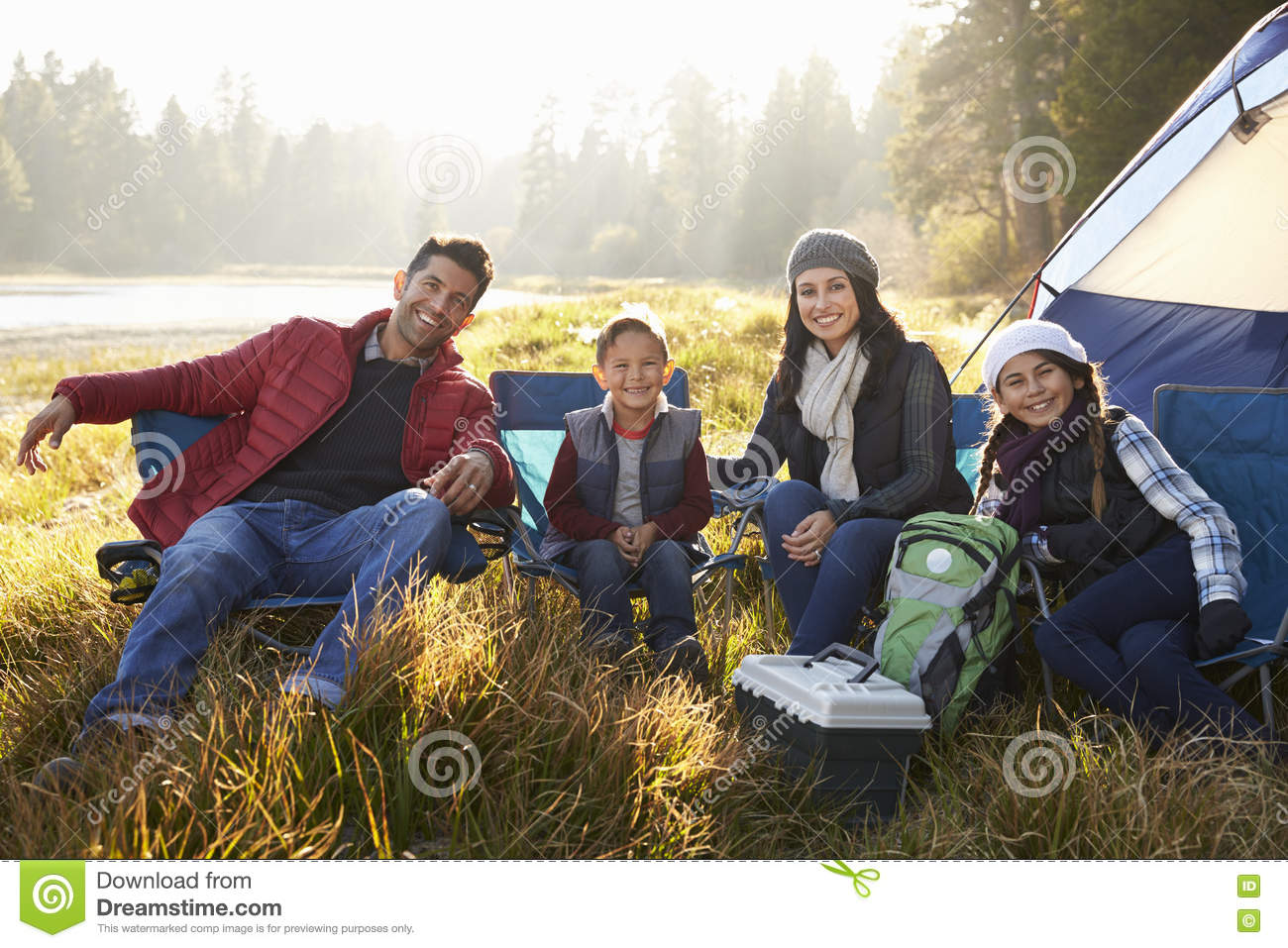 happy family on a camping trip sit by tent looking to camera stock