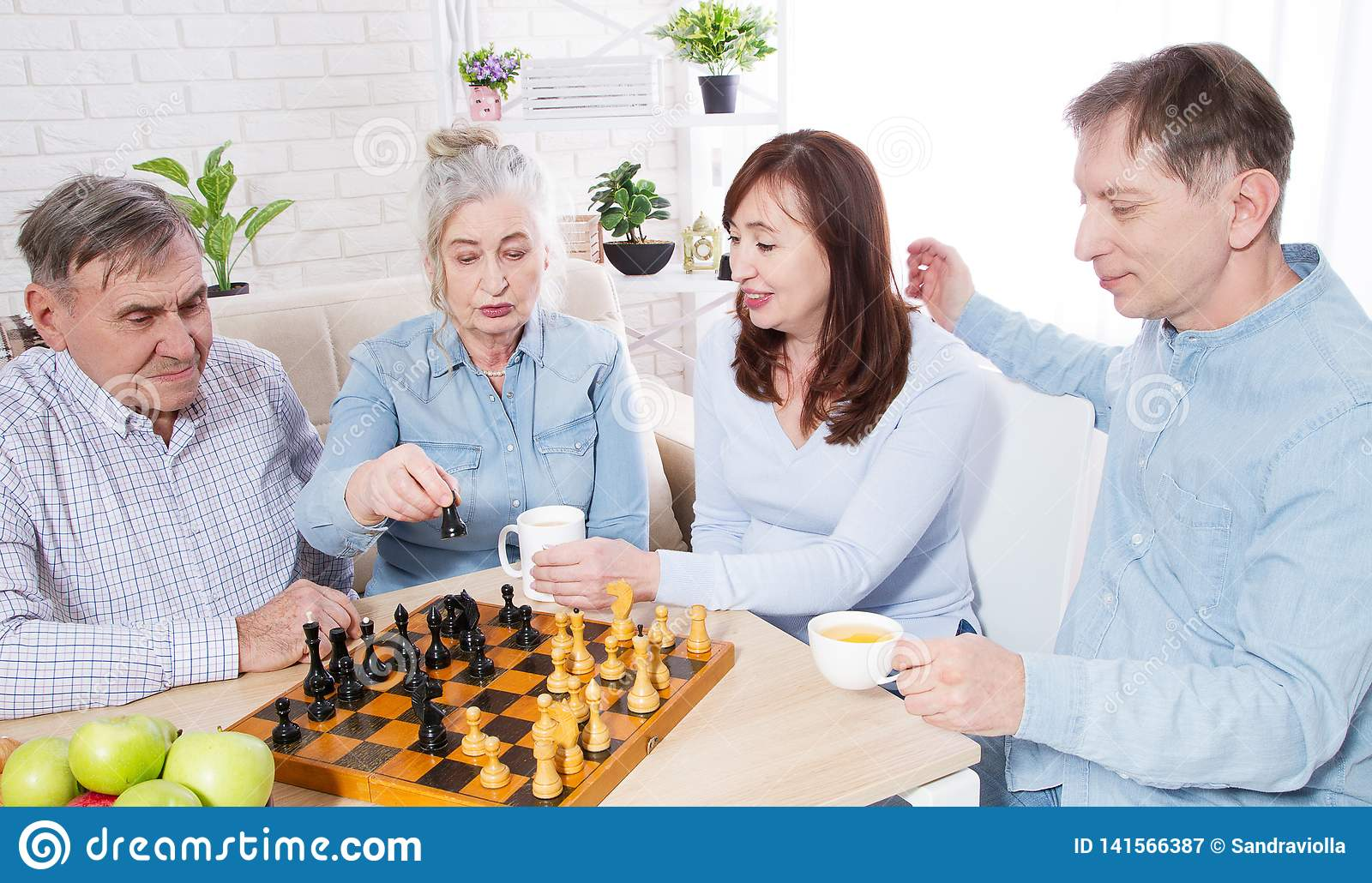 Happy family chess game time at nursing home for elderly. Parents with children have fun talk and leisure. Senior couple