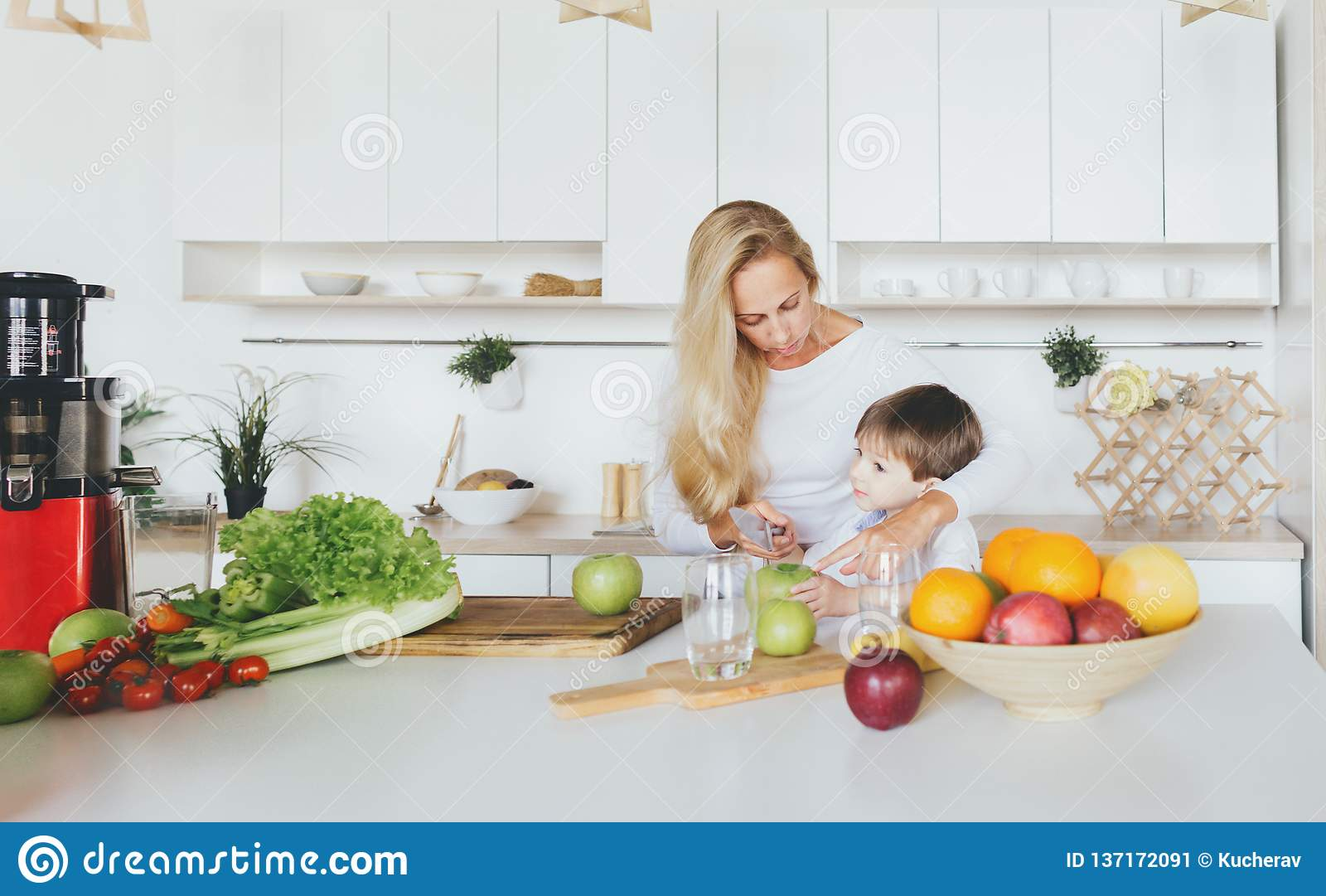 Happy family child mom cooking breakfast home in the kitchen