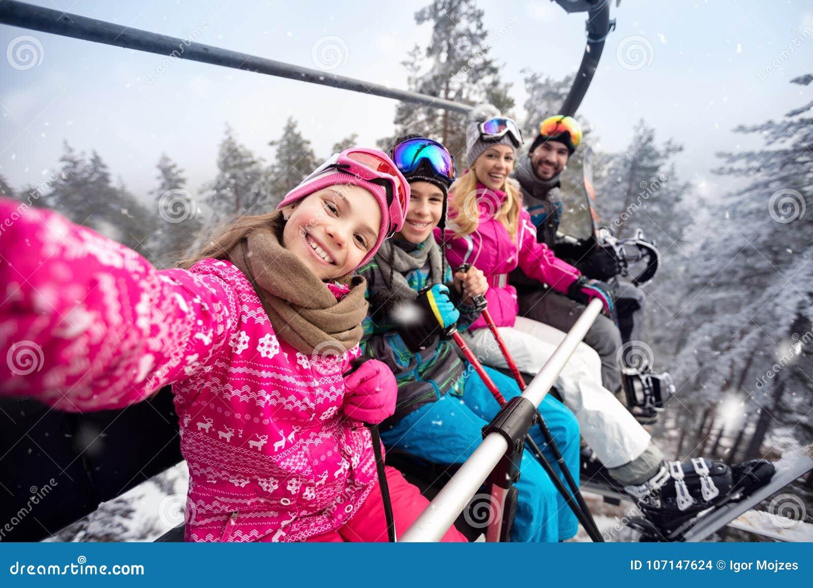 Happy family in cable car climb to ski terrain