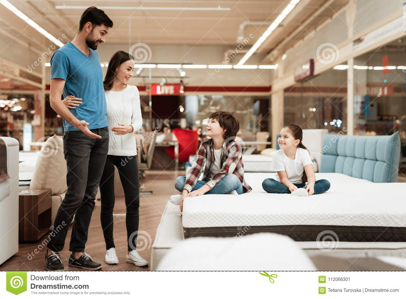 Happy family with children came in furniture store to buy mattress. Choosing mattress in store