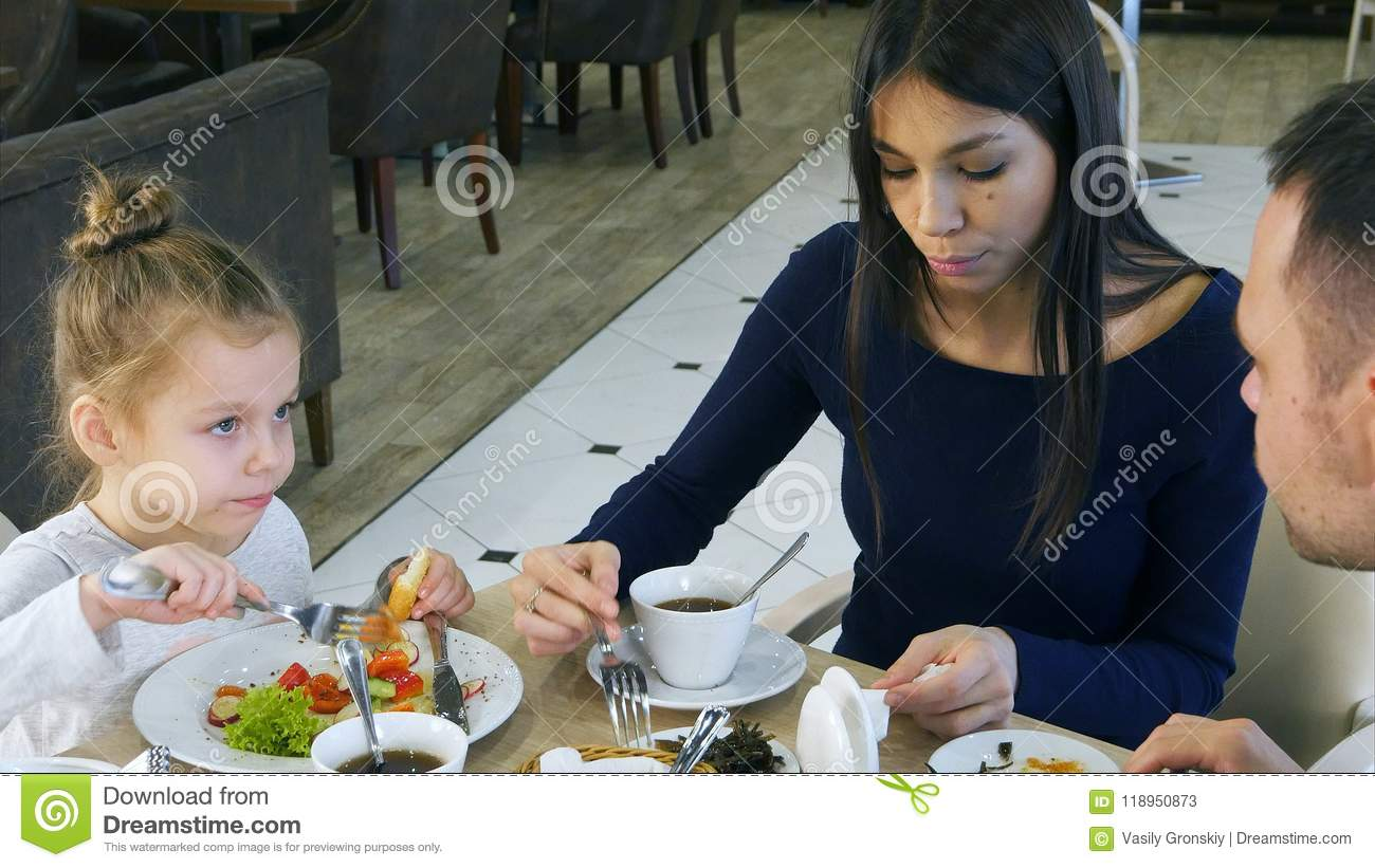 Happy family with daughter having lunch in a cafe
