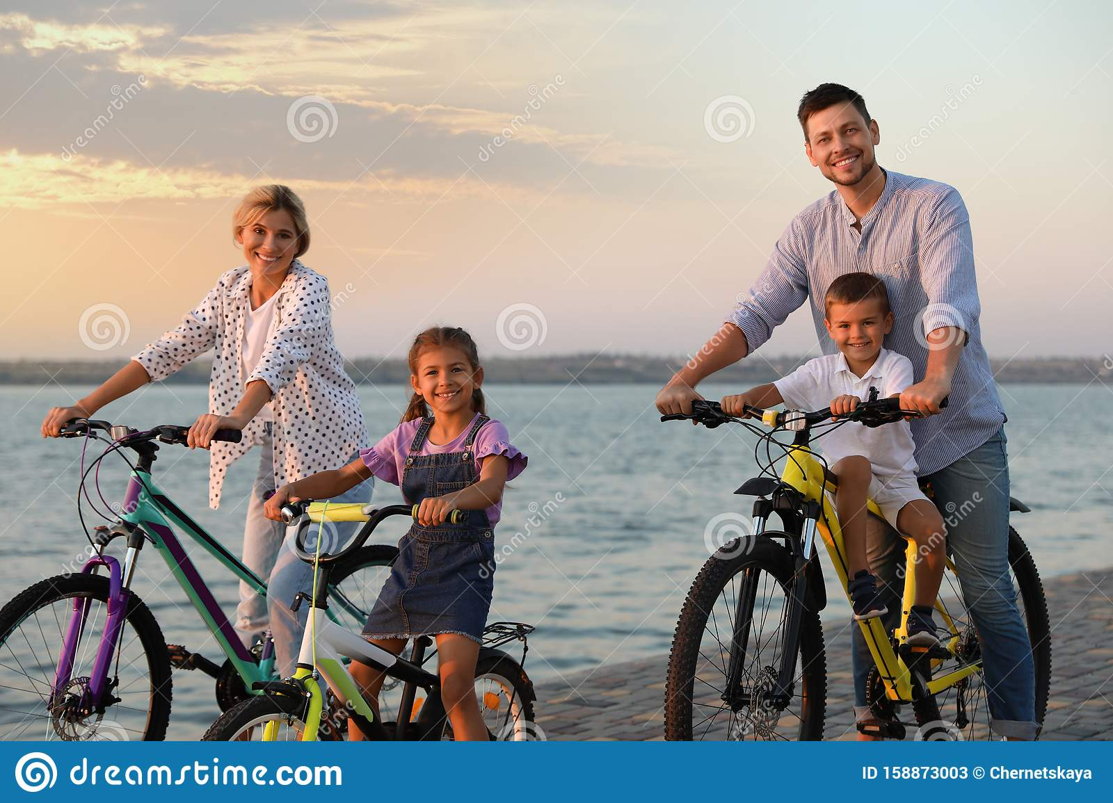 Happy family with children riding bicycles near river