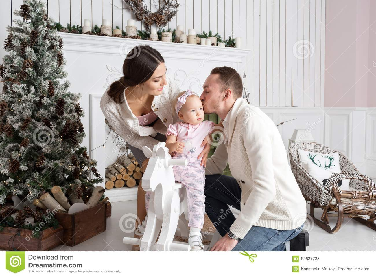 happy young family in christmas morning in home dad kisses daughter happy new year